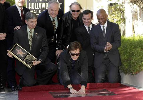 Paul McCartney touches his star on the Hollywood Walk of Fame