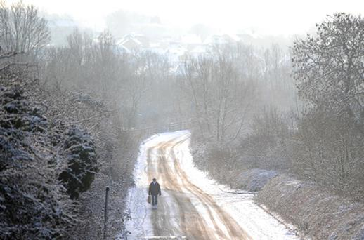 A woman walks along a snow covered road in Sixfields, Northampton, following overnight snow. Photo: PA