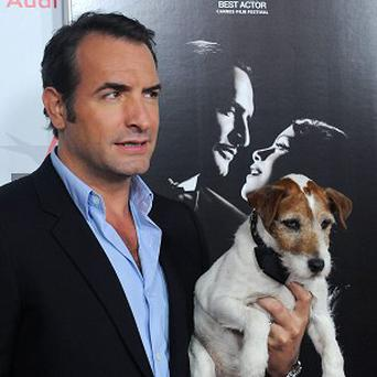 The Artist actor Jean Dujardin holds his co-star Uggie the dog (AP/Katy Winn)