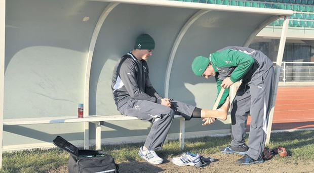 Ireland out-half Jonathan Sexton has his ankle strapped by team physio Cameron Steele at the Stade de France yesterday. Sexton tweaked a thigh muscle during kicking practice and Paddy Wallace has been drafted in as cover for tonight's game against France in Paris
