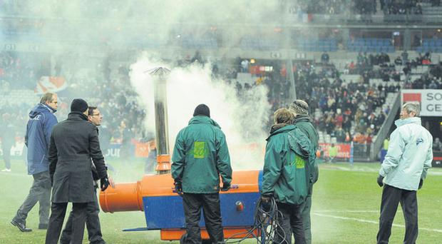 Ground staff at the Stade de France try in vain to defrost the pitch before last night's match was postponed. Photo: Matt Browne