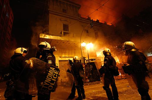 Special Police Forces stand guard as firefighters put out a blaze on Stadiou Street during the demonstration against the new austerity measures. Photo: Getty Images