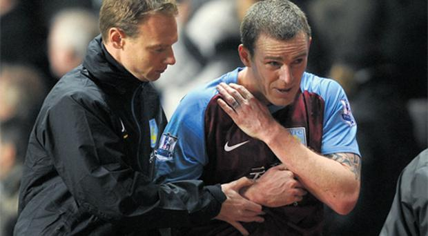Richard Dunne leaves the Villa Park pitch after being injured against Manchester City yesterday