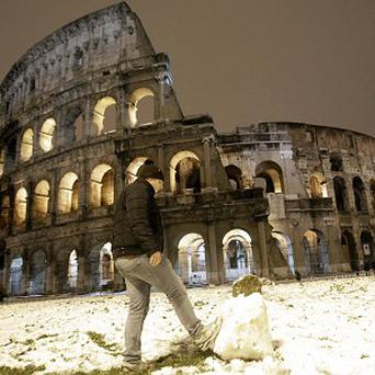 A boy plays with a snowball in front of the ancient Colosseum after a snowfall blanketed the city of Rome (AP)