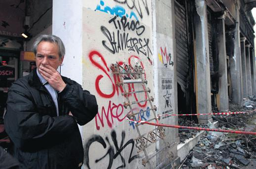 A shop-owner shocked the riot damage in Athens yesterday
