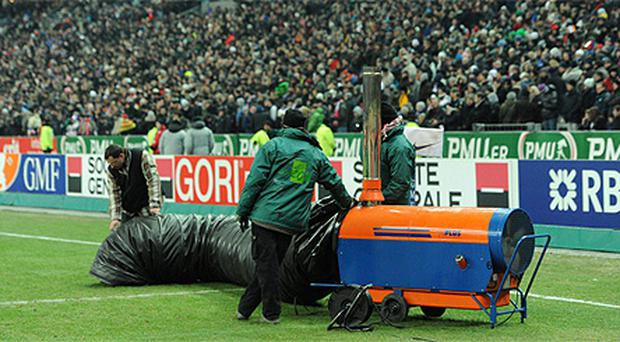 The scene at the Stade de France as workers tried in vain to thaw the frozen pitch