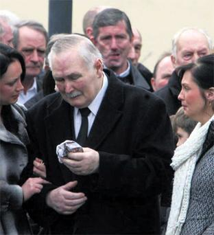 Sarah Regan's father Tom is supported by his family outside St Patrick's Church, Cloonfad, Co Roscommon, yesterday