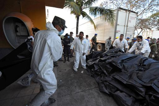 Honduran forensic workers remove corpses in plastic bags from the National Prison in Comayagua. Photo: Getty Images