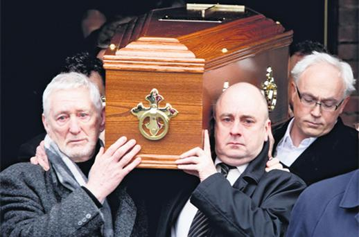 David Kelly jnr (centre) carries the coffin of his father David Kelly from the church yesterday