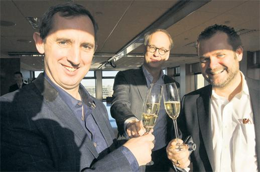 Tweak boss Jerry Kennelly celebrates the deal with Andrew McIntyre, centre, a partner with William Fry Solicitors, and Oliver Multhaup, managing director of WAZ Media Group's digital branch. Photo: Mark Condren