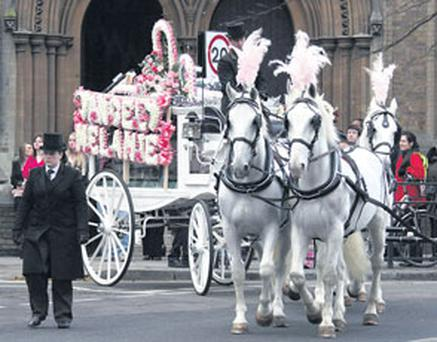 The scene at St Dominic's Priory in north London yesterday as a horse-drawn carriage removes the coffin of Melanie McCarthy McNamara from the church