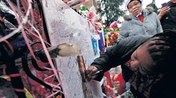 Fans leave bouquet sof roses at a makeshift memorial outside the New Hope Baptist Church in Newark, New Jersey, where the funeral of Whitney Houston takes place later today.