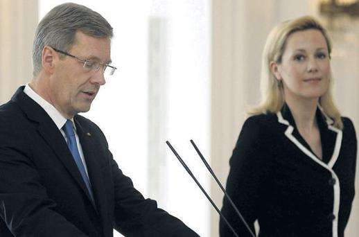 German President Christian Wulff, flanked by his wife Bettina, announces his resignation during a statement at the Bellevue Palace in Berlin yesterday, forcing a visibly shocked Chancellor Merkel to issue a statement
