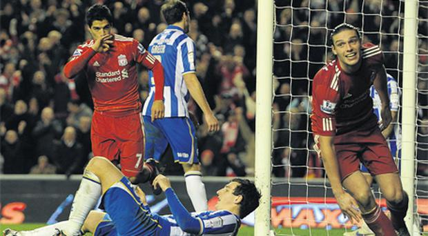 Andy Carroll (R) wheels away to celebrate after setting up Luis Suarez's goal during their 6-1 victory over Brighton in the fifth round FA Cup clash at Anfield