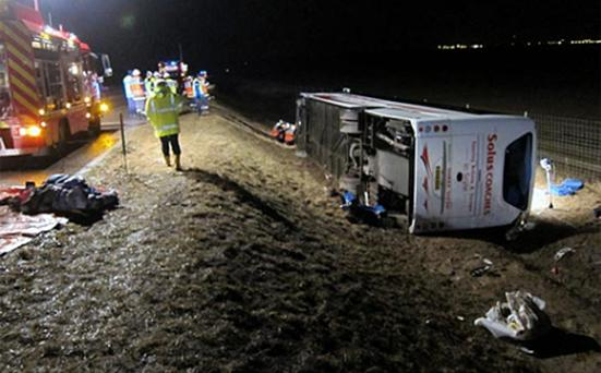 The coach lies on its side after leaving the motorway in France. Photo: AP