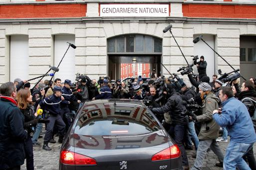 The car of Dominique Strauss-Kahn, former International Monetary Fund (IMF) head, enters the Gendarmerie surrounded by the media as he arrives for questioning by a judge investigating the so-called