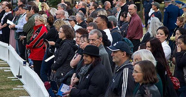 Members of the public listen to the remembrance service in Latimer Square in Christchurch, one year after a 6.3 quake hit New Zealand's second largest city