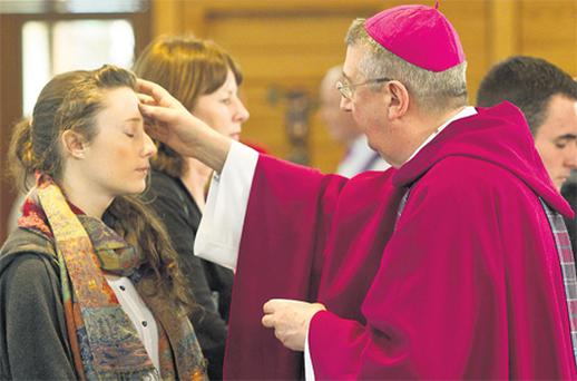 Archbishop Diarmuid Martin marks a student's forehead with the blessed ash at Mass at UCD yesterday. Photo: Mark Condren
