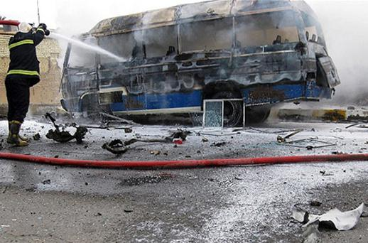 Firefighters try to extinguish a burning bus at the scene of a car bomb explosion in Baghdad, Iraq. Photo: AP