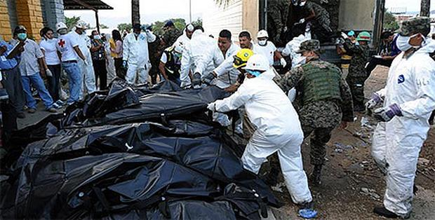 Honduran forensic officers and soldiers remove corpses in plastic bags from the National Prison in Comayagua