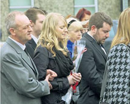 Grieving Fiona Morrissey, holding a red rose, is comforted by her father yesterday at the funeral of her boyfriend James Tynan (25), inset with Fiona. She is surrounded by members of James's family
