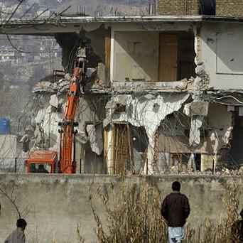Local residents watch as authorities use heavy machinery to demolish the compound of Osama bin Laden in Abbottabad (AP)
