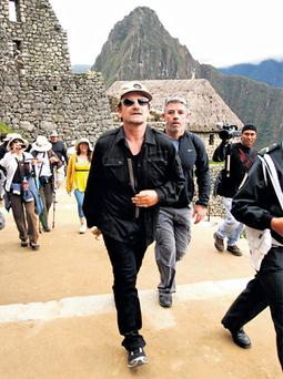 U2 frontman Bono gets a tour of Machu Picchu in Peru, to the delight of other tourists. Photo: Reuters
