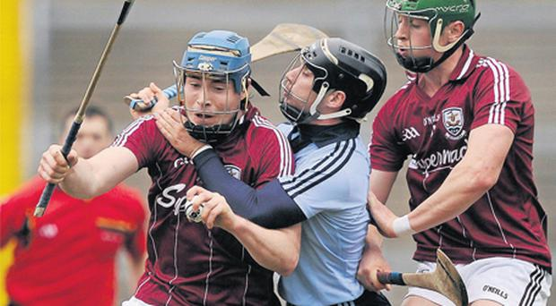Dublin's Shane Durkin gets to grips with Galway's Conor Cooney as Niall Burke arrives to support his team-mate