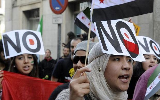 Young women with a placard reading 'No' stuck on their forehead at a demonstration against violence in Syria on February 26, 2012 in Madrid. Photo: Getty Images
