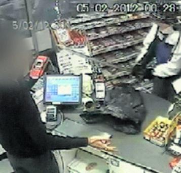 A CCTV image of the shop robber threatening the assistant with a Samurai sword