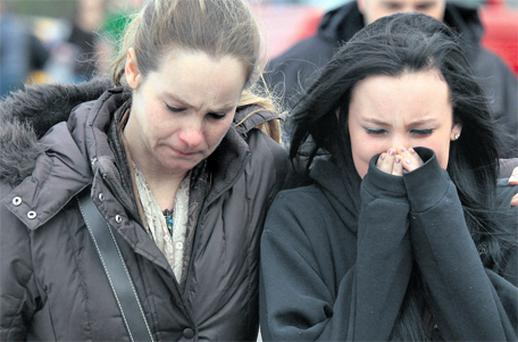 A distraught Ava Polaski, a first year, leaves school grounds with her mother Misty Polaski following a shooting in Chardon