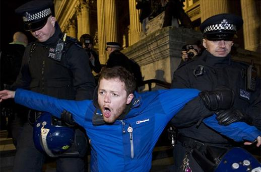 A protester is carried away by police at the Occupy protest camp outside Saint Paul's Cathedral in central London. Photo: Getty Images