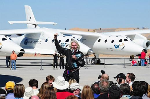 Sir Richard Branson addresses a crowd of guests and media in front of WhiteKnightTwo, with the SpaceShipTwo vessel in the middle, at Spaceport America. Photo: Getty Images