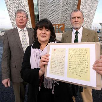 The family of Dr John Edward Simpson with a copy of the letter from their great uncle outside the new Titanic signature building in Belfast
