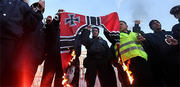 Policemen burn a Nazi flag at the parliament in Athens yesterday