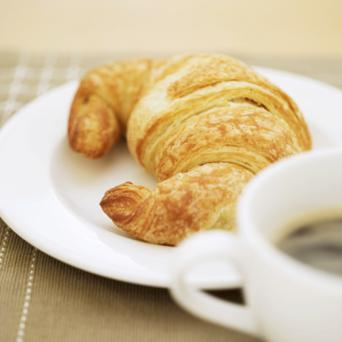 close-up of a cup of hot black coffee and a croissant
