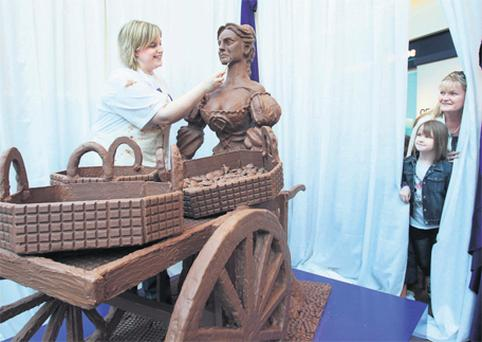 Brianna Kelly (8) and her mother Karen, from Templeogue, Dublin, sneak a look at Prudence Staite making the final touches to her life-sized version of Molly Malone
