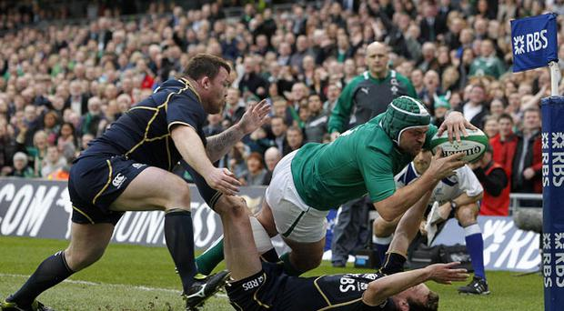 Ireland's Rory Best scoring a try despite Scotland's Mike Blair and Allan Jacobsen