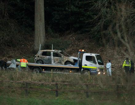 A burnt out car is removed from the scene at Ravensdale Park near Dundalk, in which two bodies were found. PRESS ASSOCIATION Photo. Niall Carson/PA Wire