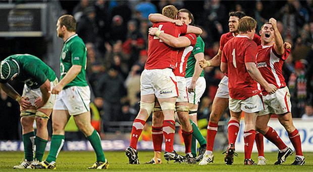 Gordon D'Arcy leaves the field as Wales players celebrate their victory over Ireland