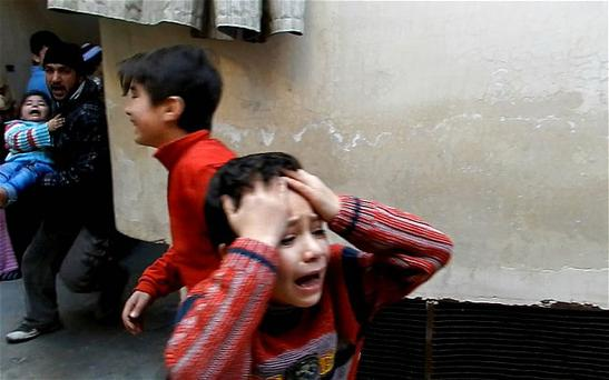 A man runs carrying a toddler as children weep during fighting in the Bab Tudmor neighbourhood of Homs.