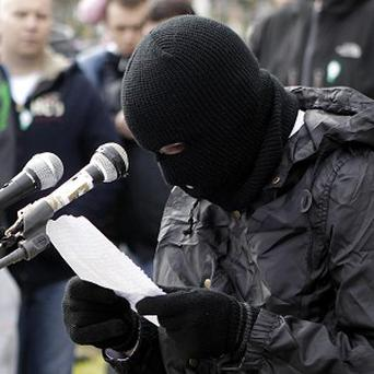 A masked member from the dissident Real IRA reads a statement to supporters at Creggan Cemetery, Derry (AP)