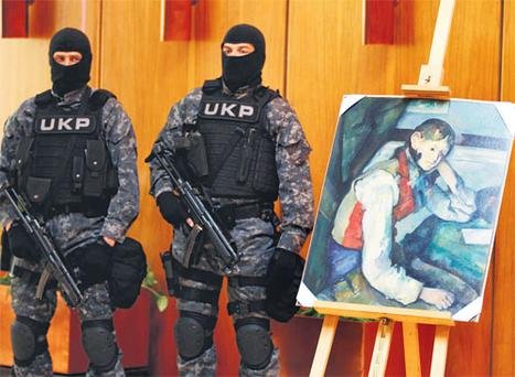 Serbian special police guard what is believed to be the masterpiece 'Boy in a Red Waistcoat' by Paul Cezanne in Belgrade yesterday.