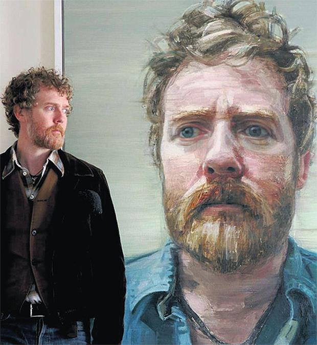 Musician Glen Hansard standing in front of 'Thread of Light', the portrait of him painted by Belfast artist Colin Davidson