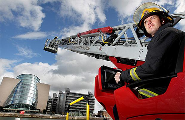 Firefighter Dermot Murray from B Watch at Tara Street Fire Station extends colleagues Cormac Wickham and Derek Clare out over the Liffey on Sir John Rogerson's Quay yesterday