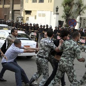 A protester is detained by security forces in front of the Saudi Embassy in Cairo (AP)