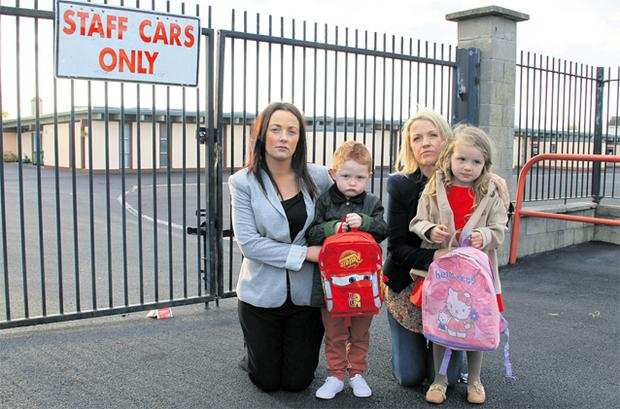 Louise Carey and her son Cillian, and Michelle Cumiskey with her daughter Indy outside St Declan's National School in Ashbourne, Co Meath, which they have been told has no room for their children