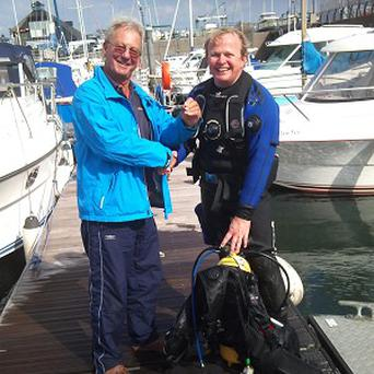 Nick King, right, from Specsavers, dived into Swansea Marina to retrieve the specs of fisherman Mike Richardson, left
