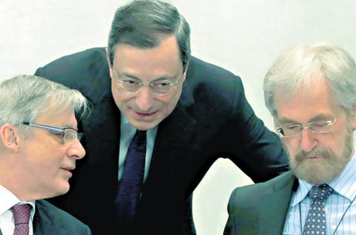 ECB president Mario Draghi speaks to France's Central Bank governor Christian Noyer and ECB executive board member Peter Praet at the central bank's meeting in Barcelona yesterday. Photo: Reuters