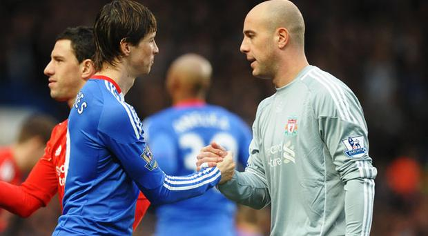 Fernando Torres of Chelsea shakes hands with former team mate Pepe Reina of Liverpool